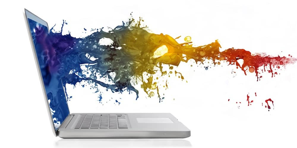 Wave of colored paint splashing out from a laptop screen to illustrate online art courses